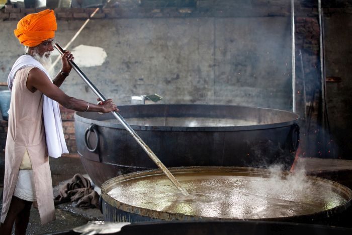 A cook in the Golden Temple cooks in an extremely large pot